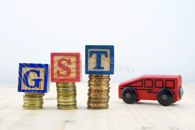 Концепция GST при деревянные блоки дальше штабелированные монеток с автомобилем игрушки стоковые изображения