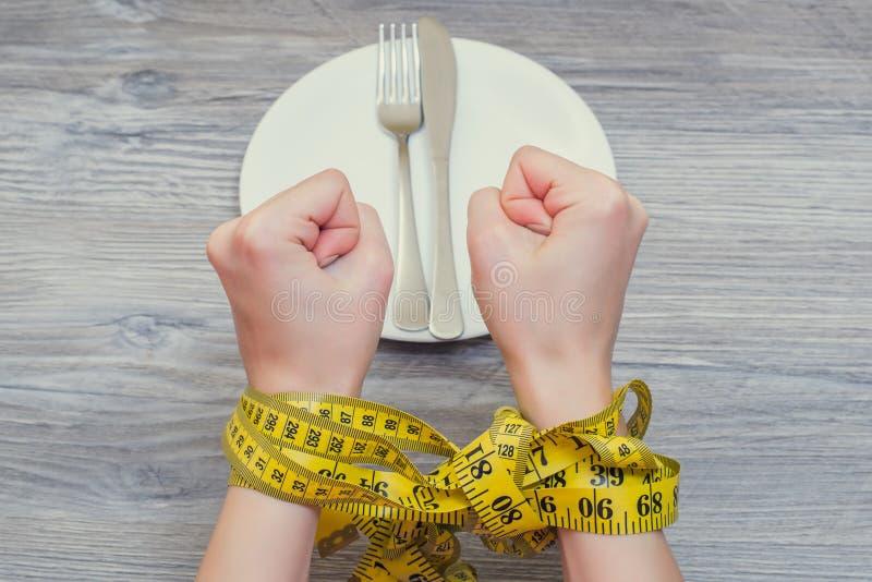 Концепция lossing веса Руки ` s женщины связанные с рулеткой стоковое фото rf