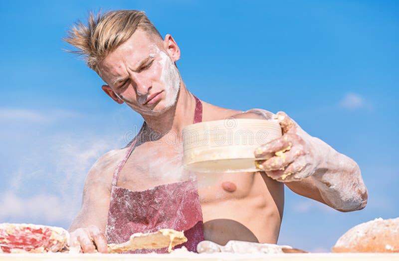 Концепция Pizzaiolo Хлебопек работая с мукой и сеткой, замешивая тестом Хлебопек или кашевар человека мышечные просеивают муку до стоковое изображение