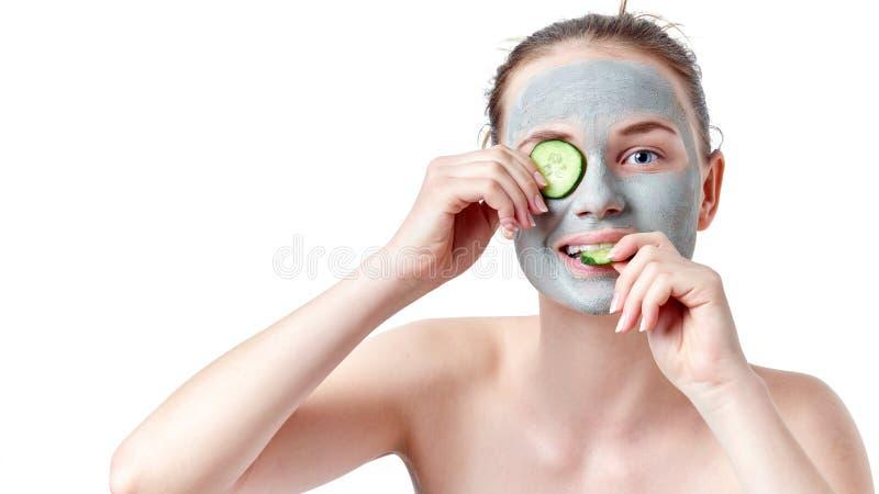 Концепция skincare подростка Девушка подростка при маска сухой глины лицевая держа 2 куска огурца стоковая фотография rf