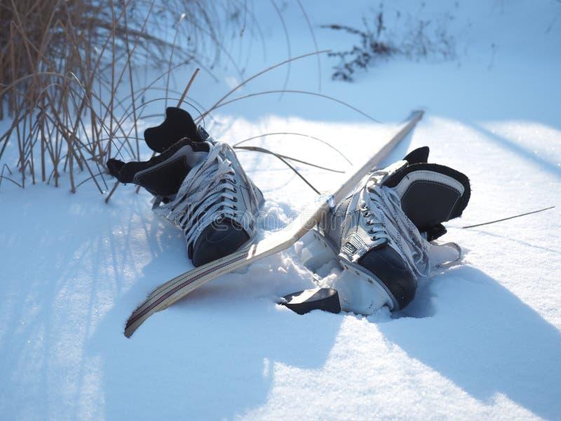 Коньки и хоккейная клюшка на озере стоковые фото