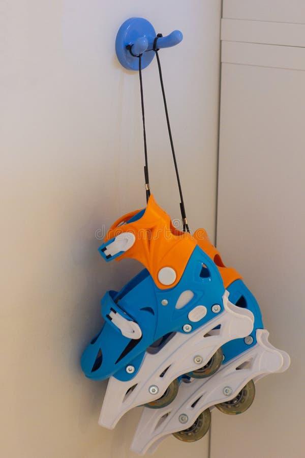 Коньки ролика вися на голубом крюке стоковые фото