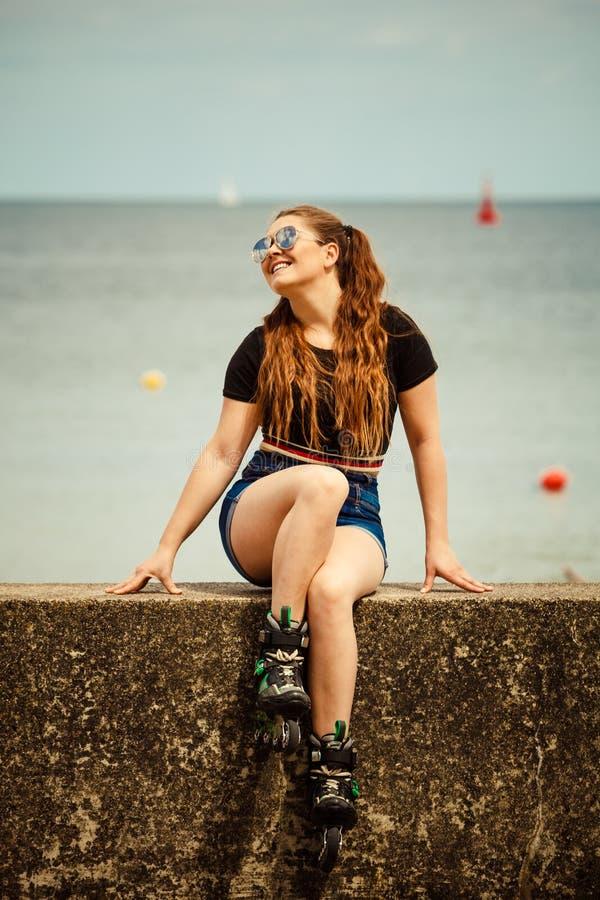 Коньки ролика счастливой молодой женщины нося стоковое фото