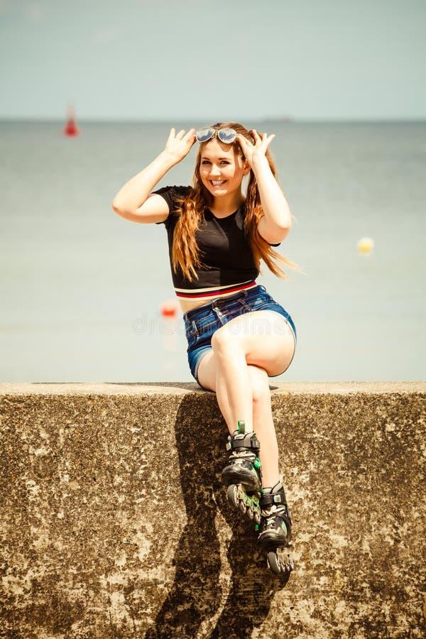 Коньки ролика счастливой молодой женщины нося стоковое фото rf