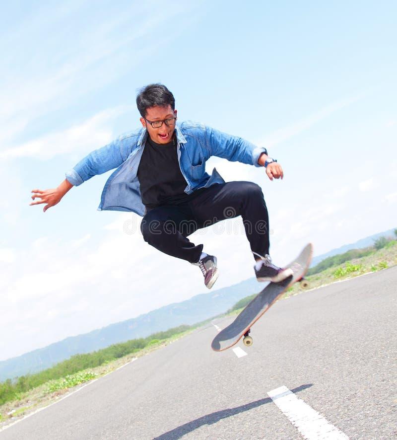 Конькобежец играя скейтборд с слегка ударять фокус стоковое фото rf