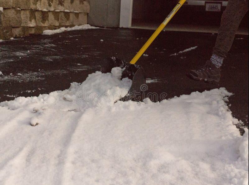 Копать снег в ее подъездной дороге стоковые изображения rf