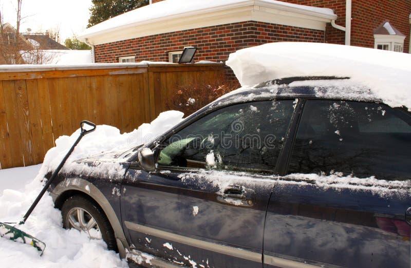 Копающ глубокий снег в подъездной дороге дома при похороненная половина автомобиля стоковые фото