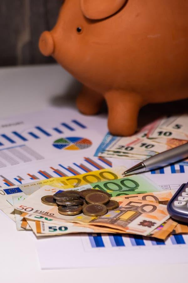 Копилка на деньгах, счетах евро и бизнес-отчетах стоковое фото rf