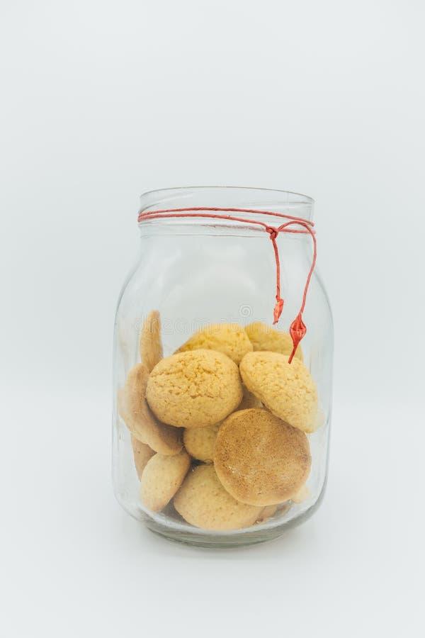 Копилка, простой стеклянный опарник заполнила с старомодными печеньями на с белой предпосылке стоковое изображение