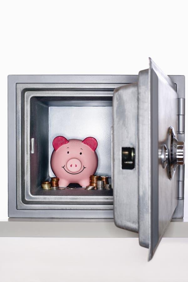 Копилка и кучи монеток в открытом сейфе стоковое фото
