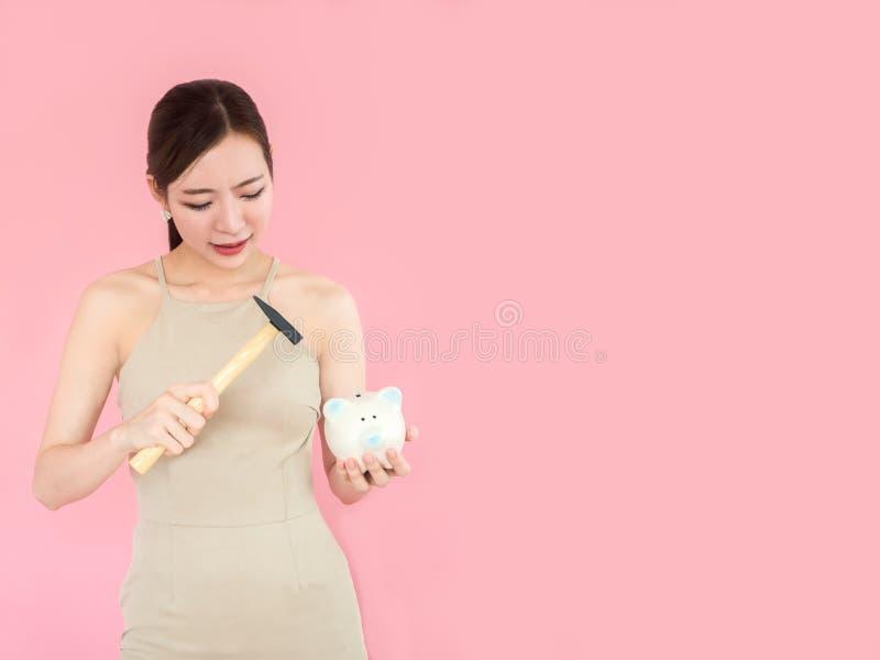 Копилка поломанная молодой женщиной с молотком стоковые изображения