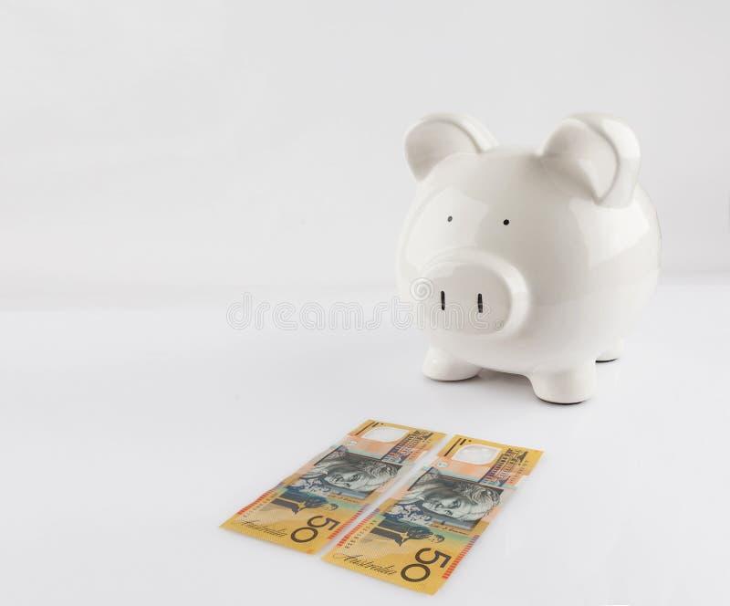 Копилка стоя около 2 долларовых банкнот австралийца 50 стоковое фото rf