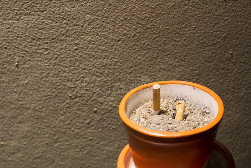 Копченые сигареты в ashtray на ноче стоковое изображение