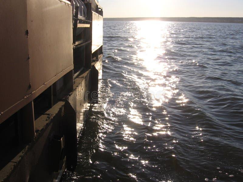 корабль баржа плавая на волны в море путешествуя вода сверкнает в солнце стоковое фото