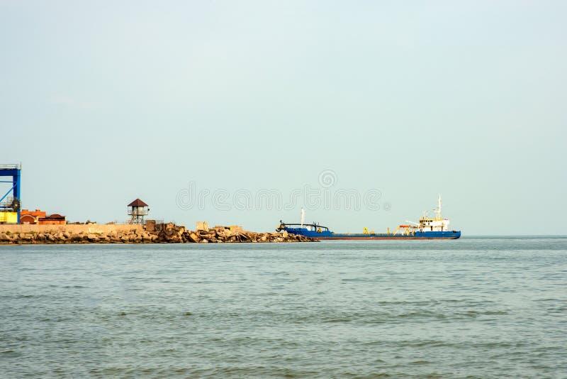Корабль входит в морской порт для погрузки или разгрузки груза стоковая фотография