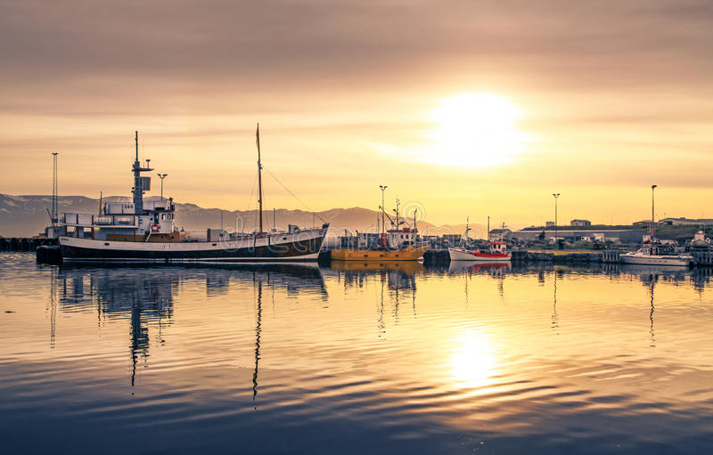 Корабли лежа в гавани Husavik на заходе солнца, Исландия стоковое фото rf