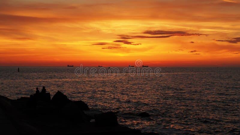 Корабли и оранжевые облака на заходе солнца стоковое изображение