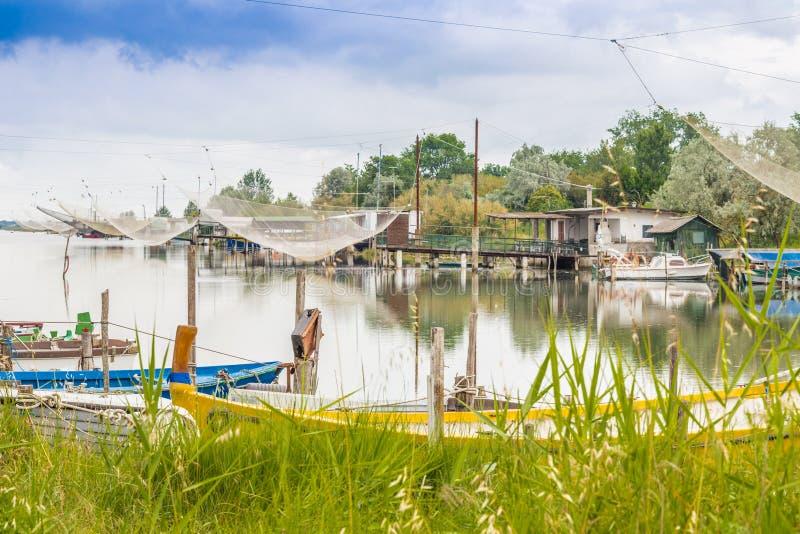 Корабли и хаты рыбной ловли в тиши brackish лагуны стоковые изображения