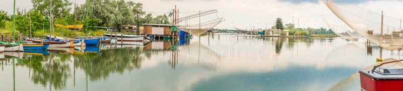 Корабли и хаты рыбной ловли в тиши brackish лагуны стоковая фотография