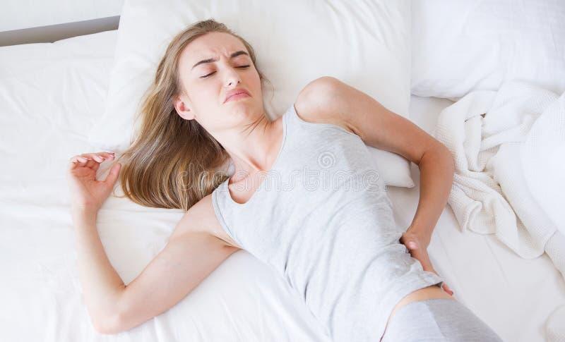 Корейская, азиатская женщина, боль в спине девушки и сидит на кровати в спальне в утре, плохой кровати, концепции здравоохранения стоковые изображения