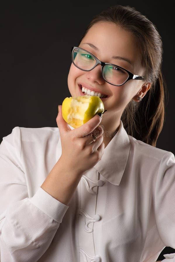 Корейская красивая усмехаясь девушка есть зеленое яблоко стоковое изображение rf