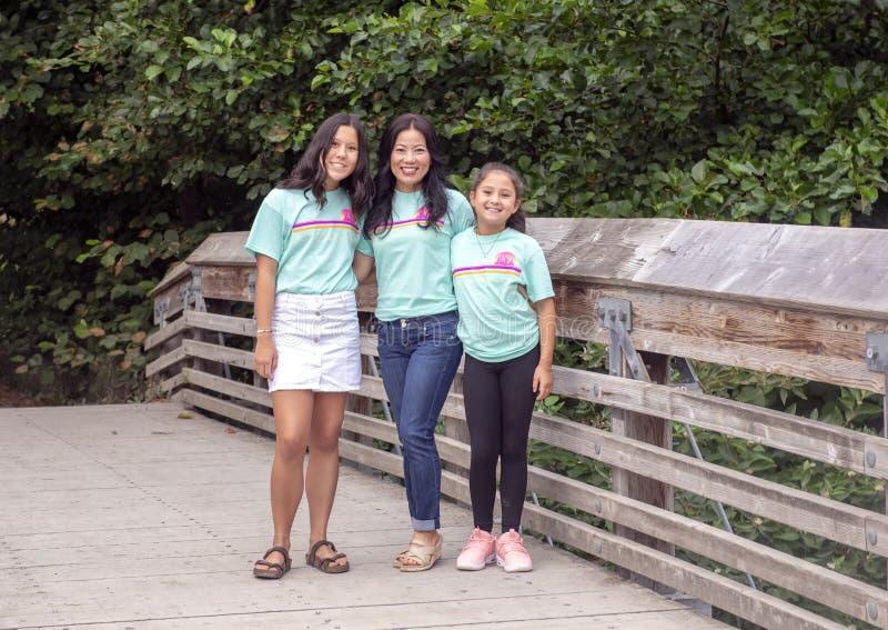 Корейская мать представляя с ее дочерьми Amerasian в дендропарке парка Вашингтона, Сиэтл, Вашингтон стоковые изображения