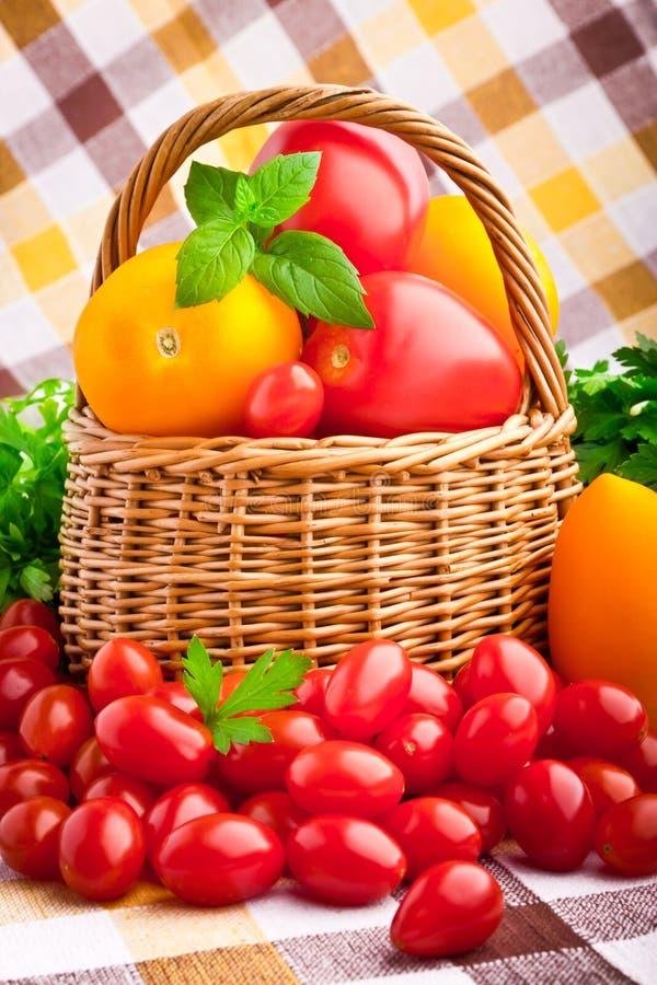Корзина вполне свежих томатов и томатов вишни стоковая фотография rf