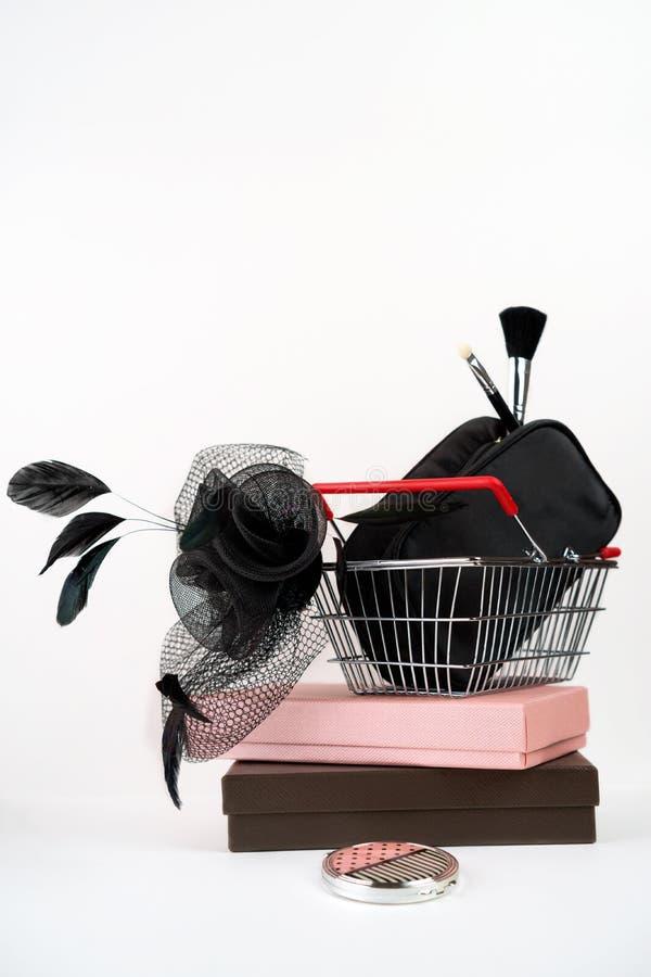 Корзина для товаров с черной женской шляпой с вуалью в ретро стиле и сумка с составляют на подарочных коробках и белой предпосылк стоковые изображения rf