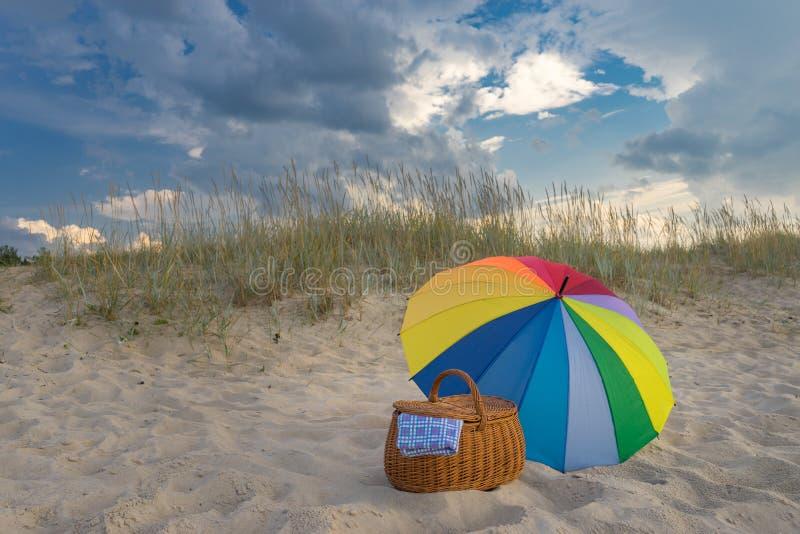 Корзина зонтика и пикника против пляжа и облаков стоковое изображение
