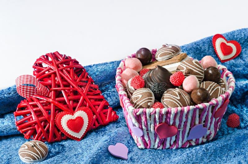 Корзина конфеты, печенья и сердца декоративные дня валентинок на голубой предпосылке белизны ткани бархата стоковое изображение