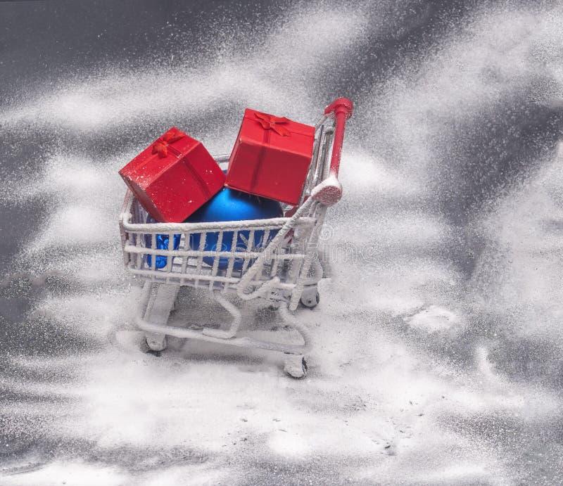 Корзина, красная подарочная коробка и голубой глобус с белым покрытым снегом стоковая фотография