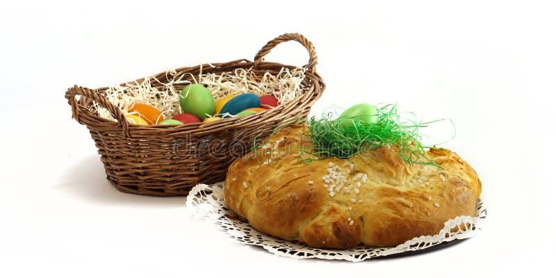 Корзина пасхи с косичкой хлеба пасхальных яя и печениь дрожжей стоковая фотография