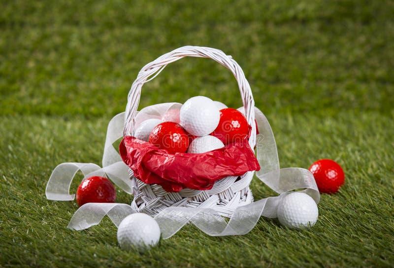 Корзина пасхи с шарами для игры в гольф и лентами стоковое изображение