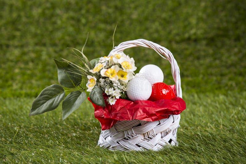 Корзина пасхи с шарами для игры в гольф и цветками стоковая фотография