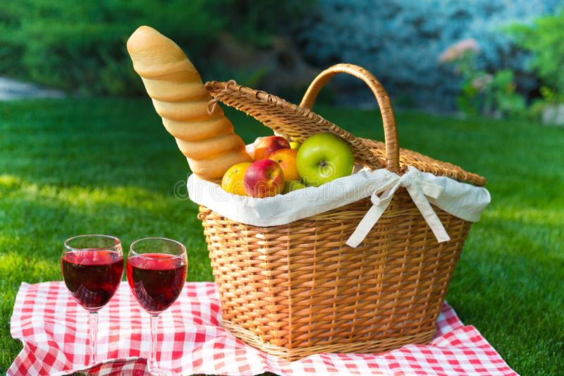 Корзина пикника с плодоовощами и хлебом на лужайке стоковое фото