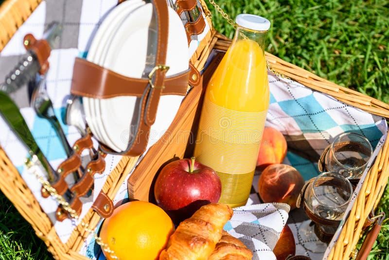 Корзина пикника с плодоовощами, соком и круассанами стоковые фотографии rf