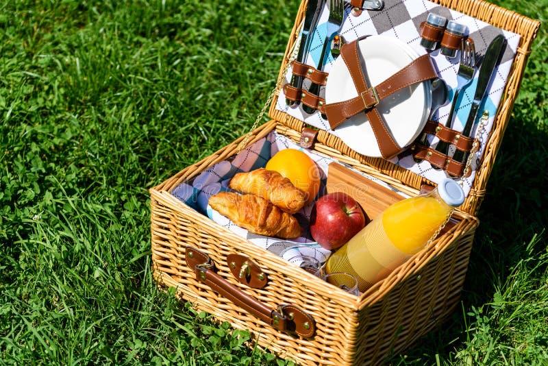 Корзина пикника с плодоовощами, соком и круассанами стоковое изображение rf