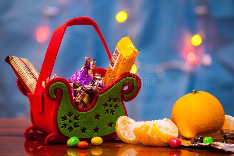 Корзина праздничного подарка рождества Сани рождества конфеты сюрпризов Конфета, печенья, tangerines стоковое фото rf