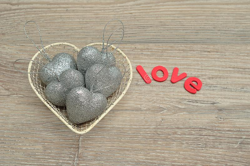 Корзина провода заполнила с серебряными безделушками формы сердца и влюбленностью слова стоковая фотография rf