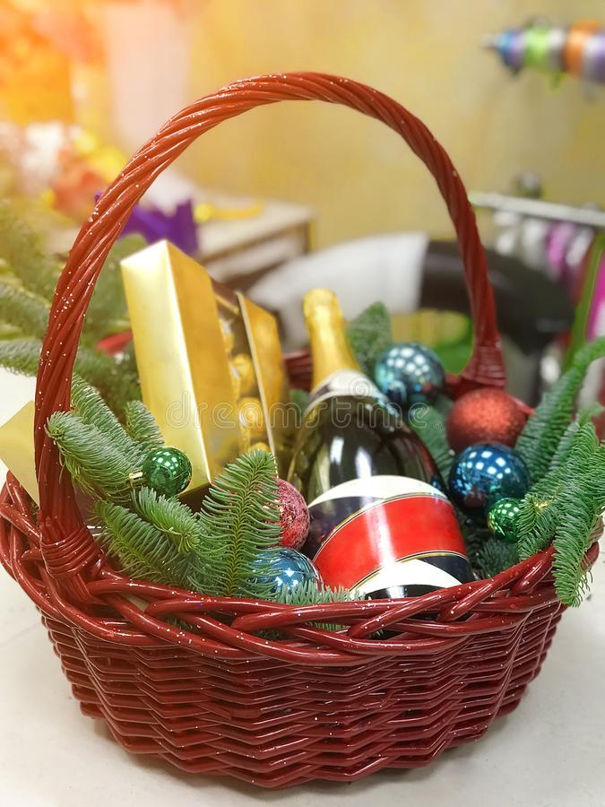 Корзина рождества с бутылкой помадок шампанского и ветвей подарка спруса- стоковое изображение rf
