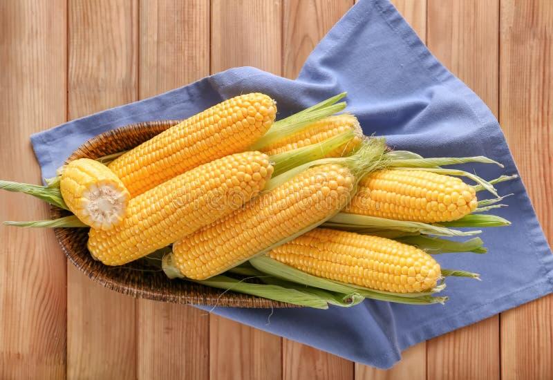 Корзина с вкусными стержнями кукурузного початка на деревянном столе стоковое изображение rf