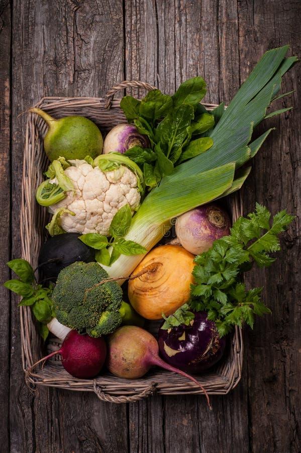 Корзина с овощами на деревянной предпосылке Цветная капуста, брокколи, редиска, пастернак, лук-порей, кольраби стоковые изображения
