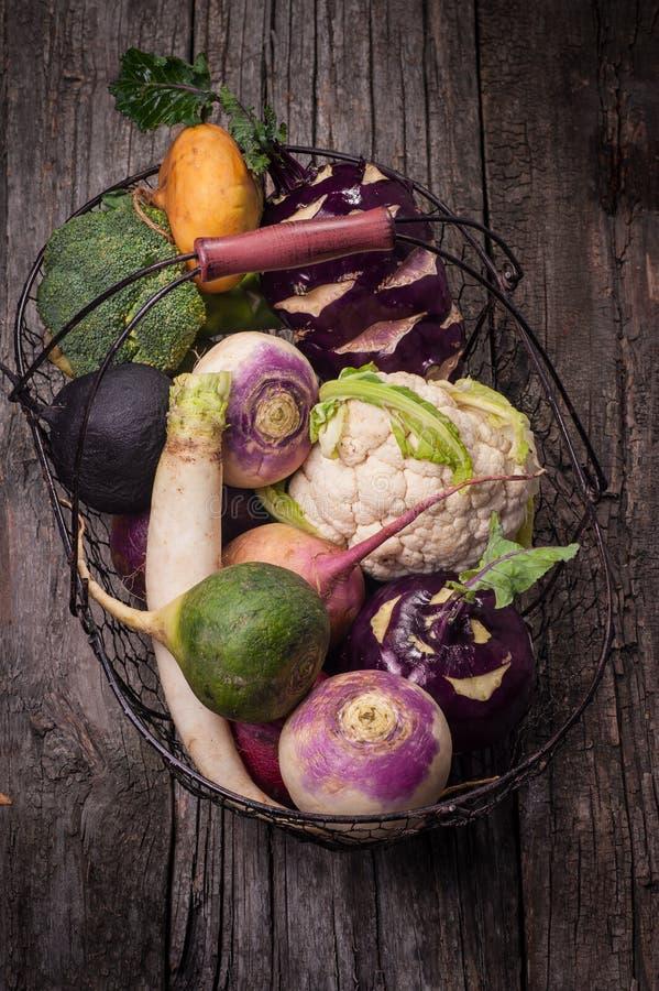 Корзина с овощами на деревянной предпосылке Цветная капуста, брокколи, редиска, пастернак, лук-порей, кольраби стоковая фотография rf