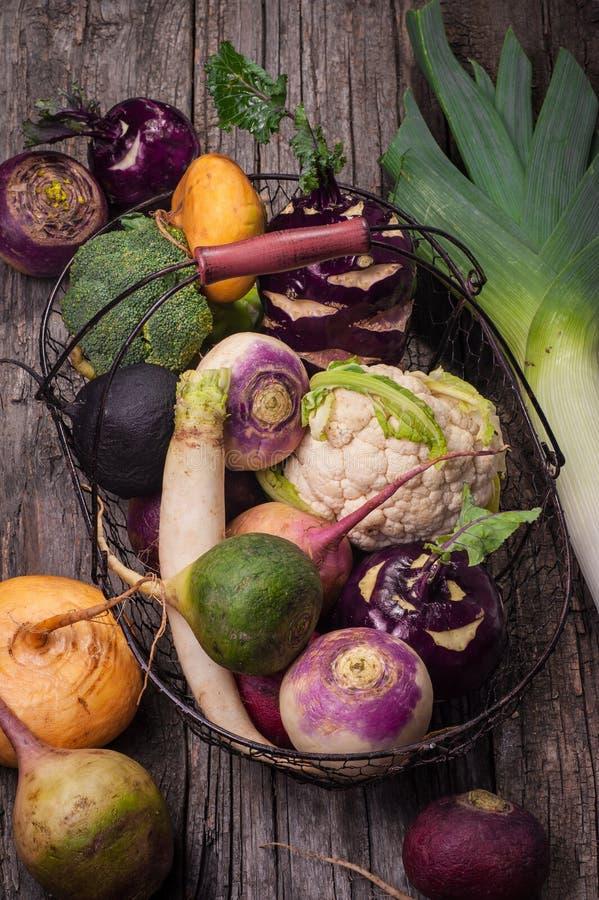 Корзина с овощами на деревянной предпосылке Цветная капуста, брокколи, редиска, пастернак, лук-порей, кольраби стоковое фото