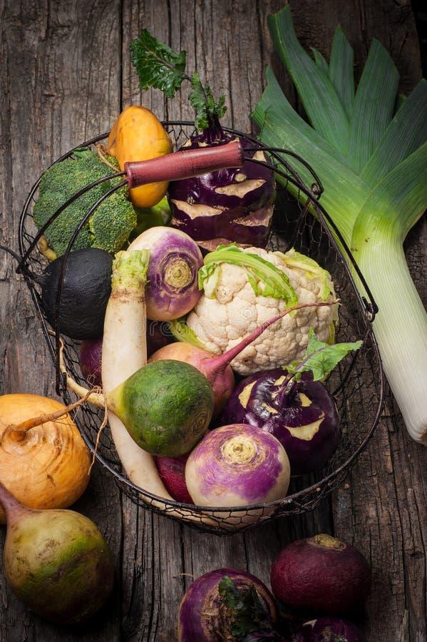 Корзина с овощами на деревянной предпосылке Цветная капуста, брокколи, редиска, пастернак, лук-порей, кольраби стоковое фото rf