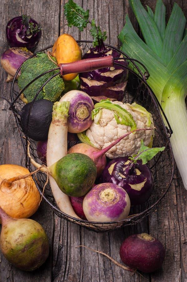Корзина с овощами на деревянной предпосылке Цветная капуста, брокколи, редиска, пастернак, лук-порей, кольраби стоковая фотография