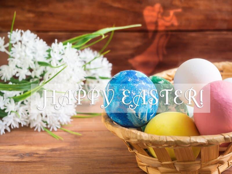Корзина с пасхальными яйцами и букетом цветков на деревянной предпосылке стоковые изображения