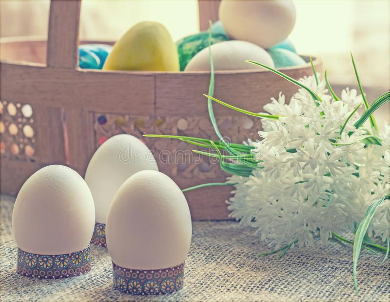 Корзина с покрашенными пасхальными яйцами и букет белых цветков стоковые изображения rf