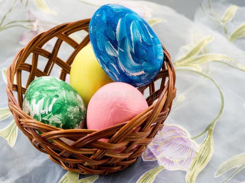 Корзина с покрашенными пасхальными яйцами на светлой предпосылке стоковые изображения