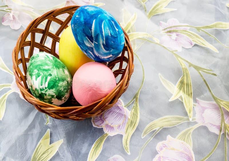Корзина с покрашенными пасхальными яйцами на светлой предпосылке стоковые фото